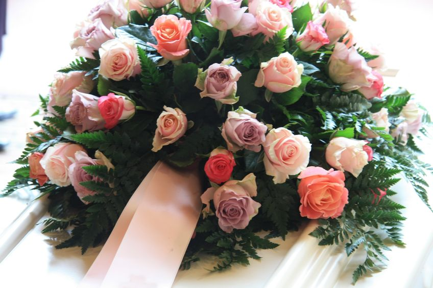 10433838 - pink sympathy flowers with a pink ribbon on a white coffin