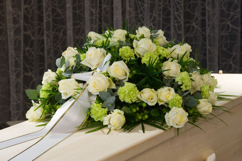 52023244 - a coffin with a flower arrangement in a morgue