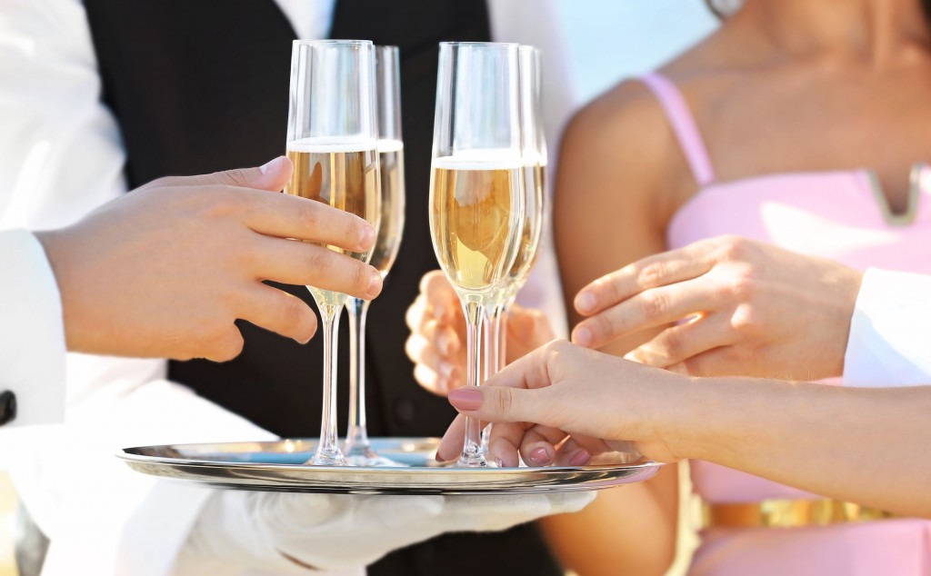 97092489 - waiter offering champagne to guests at party, close up view