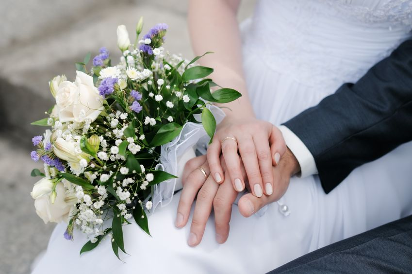 9979073 - bride and groom's hands with wedding rings and bouquet of flowers